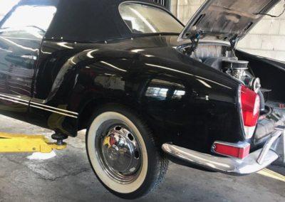 Black car on lift in shop